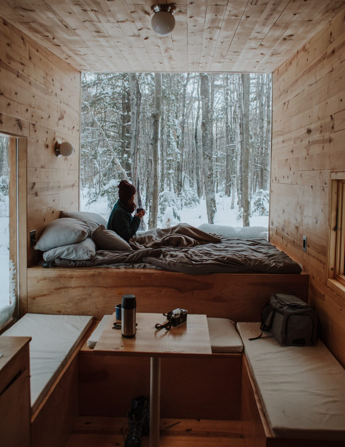 Woman sipping drink in log cabin looking out of the window onto snowy forest