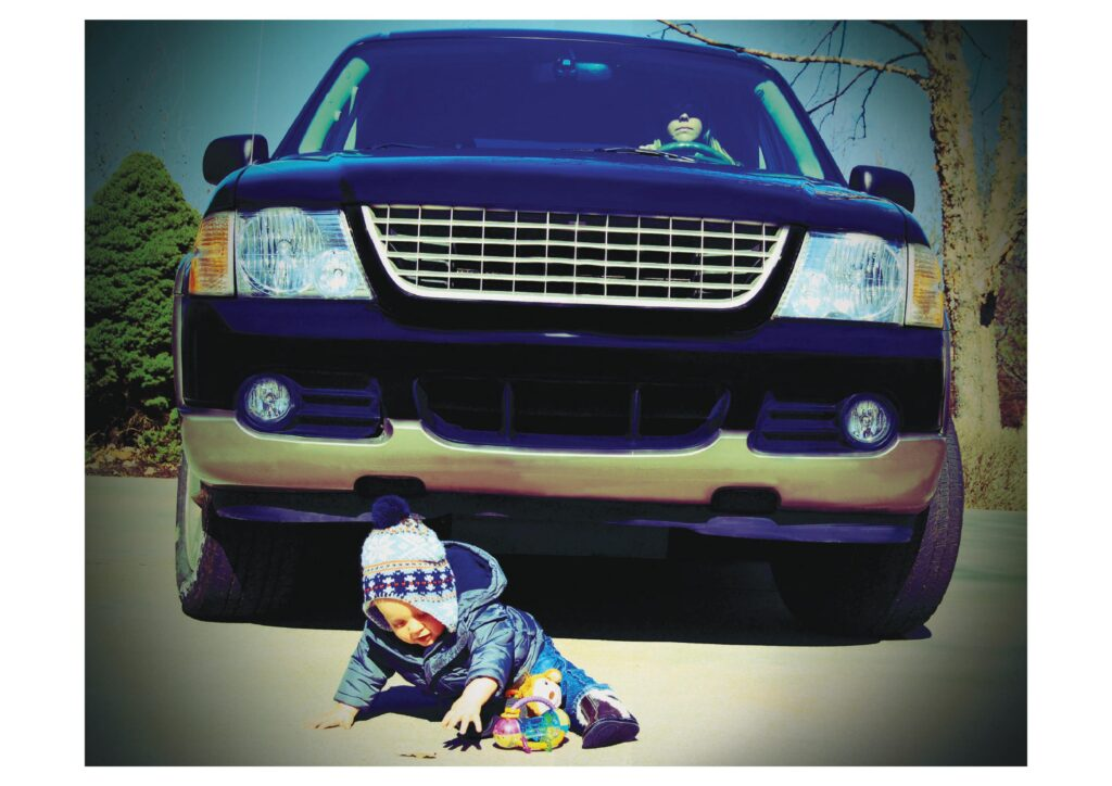 Very young child playing in front of massive SUV